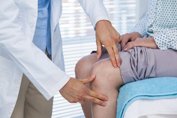 Doctor examining patient knee